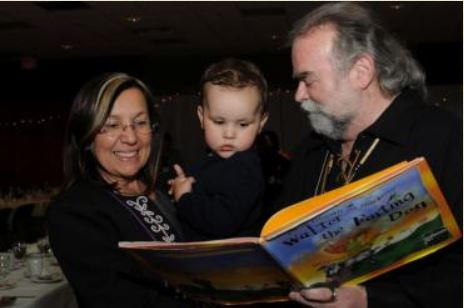 Marie Battiste reading a book with toddler